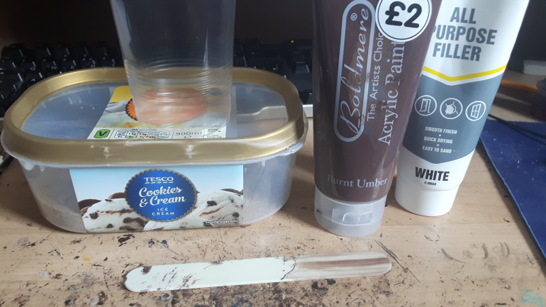 Time to make some texture paint.  Here we have a disposable pint glass to mix it in.  A tongue depresser for stirring.   An ice cream tub full of sand.  Some cheap filler in a squeezy tube and some cheap dark brown paint.