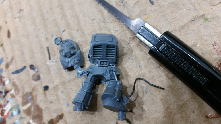 I cut the models torso from the legs, again using the saw. I found out that it works best to cut below the oval detail on the back. Also the front part of the model came loose during this step.