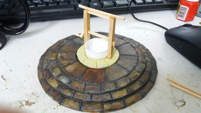 So initial build, I made a circle of milliput the right diameter and textured it and created the flag stones, then while still wet I placed the well wall form (an old bottle cap) and the coffee stirrer uprights.