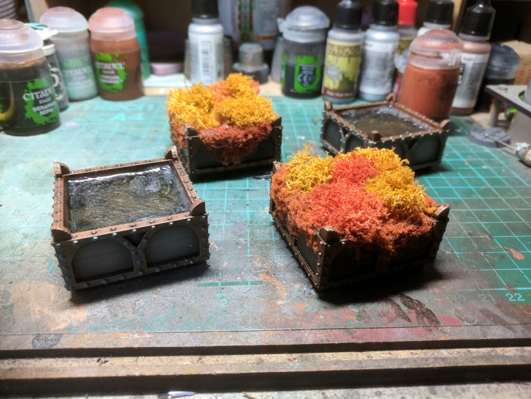 Painted up the boxes using standard dark metal and brass colours then added in the resin to a couple and glued the lichen into the others.