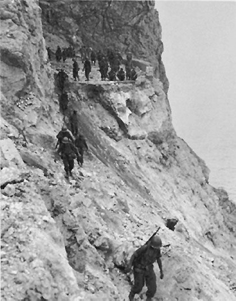 US 30th Infantry advancing along a destroyed coastal road