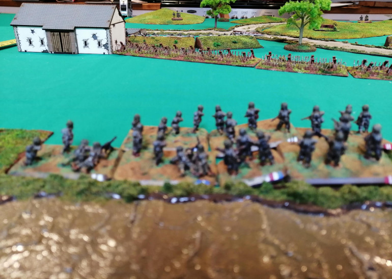 Assault Platoon A looks at the barbed wire the defending Germans dug in behind