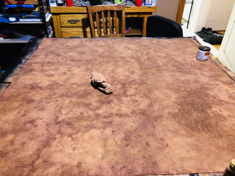 """The base of the table is a mat made from a canvas drop cloth coated with acrylic caulk, textured with sand and painted in with the colors chosen in the last post, when this was dry it was washed with a homemade wash a mixture dark brown, black and red. This was was applied in sections and then """"sponged"""" off with paper towel to give the variations in colors and the mottled look it has"""