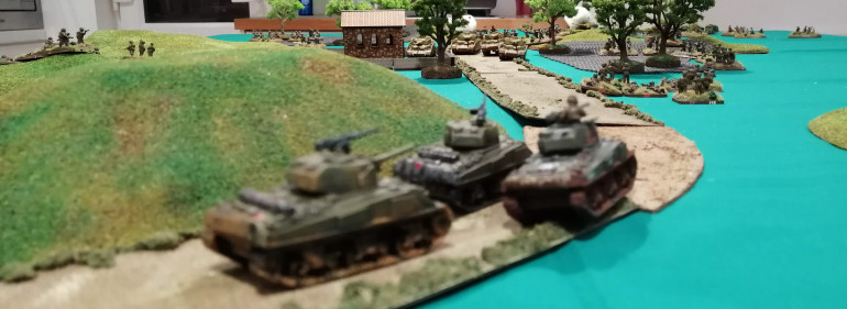The Shermans 'Blitz' around the hill and try to line up the Panzers