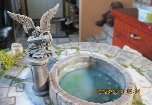 GW angel with amphora made from Milliput, a paper clip, and a GW elf bit. Note the leaves in the water. They were made with a Green Stuff leaf cutter and painted paper.