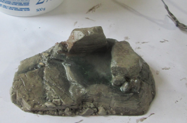 Tan base colour applied to rocky areas, while any areas to be covered with foliage had a dark green shadow colour applied. It was given a brown wash, in this case a homegrown glop of water, craft paint, and dish soap, and set aside to dry.