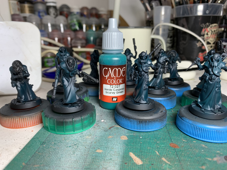 Basecoat on the, er, coats. Vallejo Scurvy Green through a Badger Krome airbrush, aiming for the raised areas. I'm trying to go for a deep inky look to the models.
