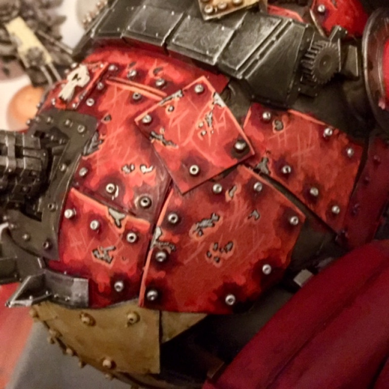 Finally, using Wild Rider Red and Lugganoth Orange, highlight the chips by painting a thin line along the bottom edges of each blotch. Dot the rivets with Runefang Steel (they'll each receive a wash and some streaking in a later stage)