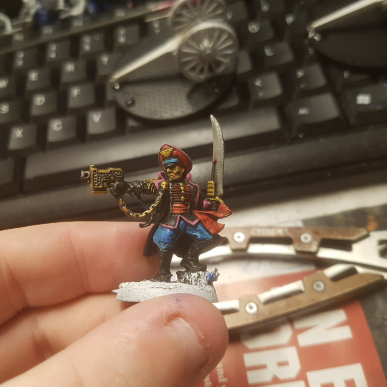 Any Attached Elements such as Techpriests, Fleet Officers or Commissars Retain their Old Equipment Although they will Often add a Trim to Represent the Unit they are Fighting With. Here we can See a Commissar Trimmed with the Pink of the Infantry.