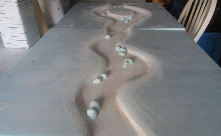 Two river boards, one with an island. After carving out the channel I lined it with wall filler, both to protect the foam in case the Woodland Scenics stuff ate it, and also to texture the bottom (I didn't like the texture and ended up sanding it smooth). I also used polystyrene to make some larger rocks for the banks and river bed. The foam has warped on the island board, but I'll weigh it all down on a flat level surface when I do the first pour of Realistic Water.