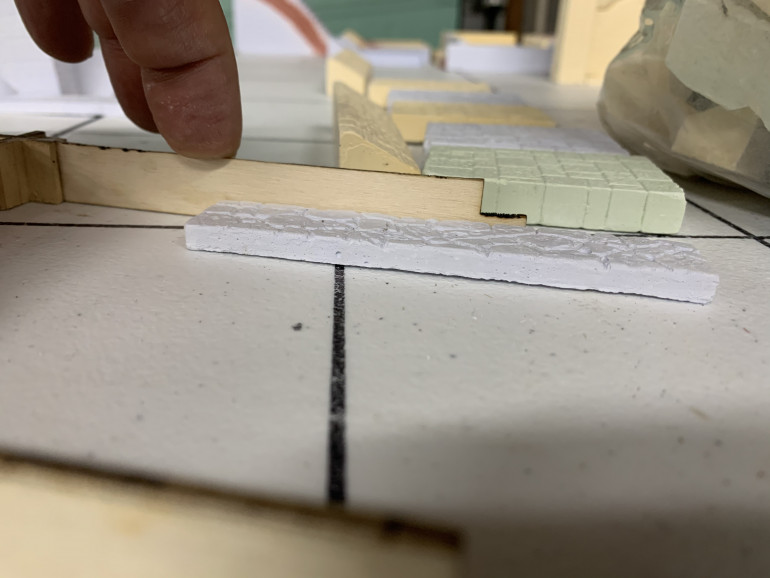 This MDF gauge is what is used to slice the hexes to their proper size. My plan is eventually to make stone walkways with grass on both sides and to do that, I need to see how tall the plaster walkways are when compared to the height of a half height hex. Close enough for my liking. Check 2.