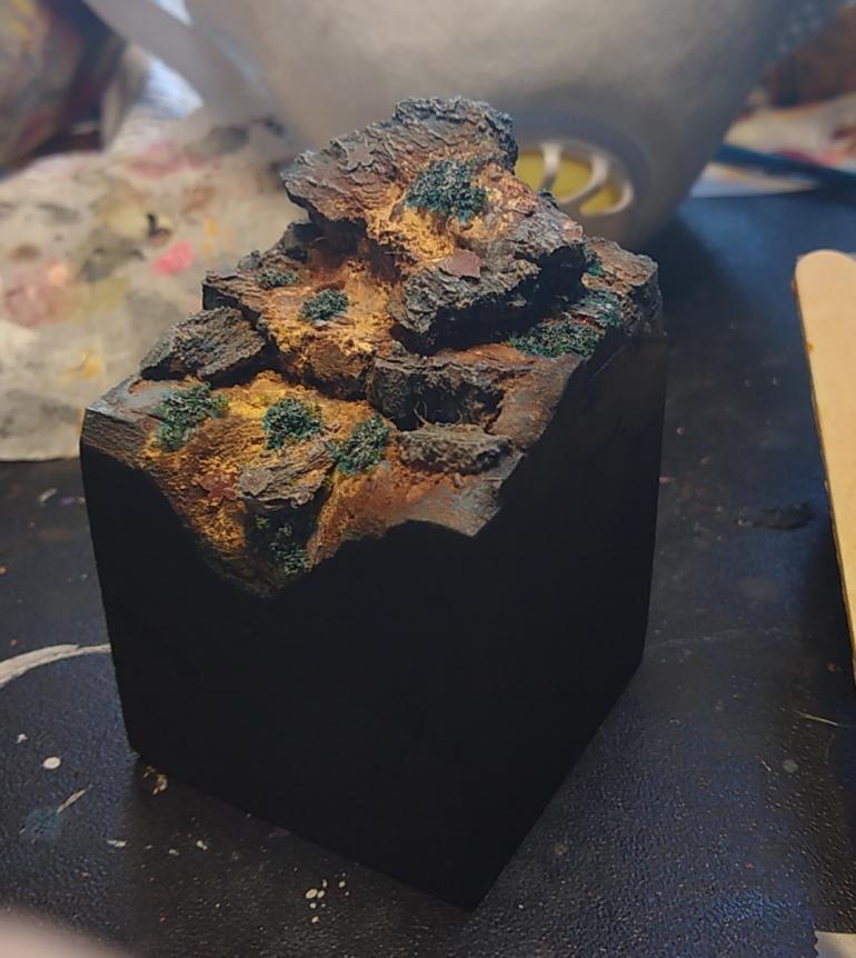 I used some fine clump flock soaked in super glue, painted with bluegreen ink, and then drybrushed with grey to create some moss/lichenish vegetation.