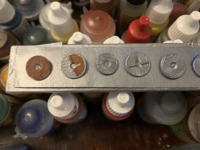 A mix of Oathmark and Gripping Beast plastic shields primed with Army Painter Plate Mail Metal primer. The wooden elements are being painted Army Painter Fur Brown. This will require at least two thin coats of the Fur Brown to get good coverage.