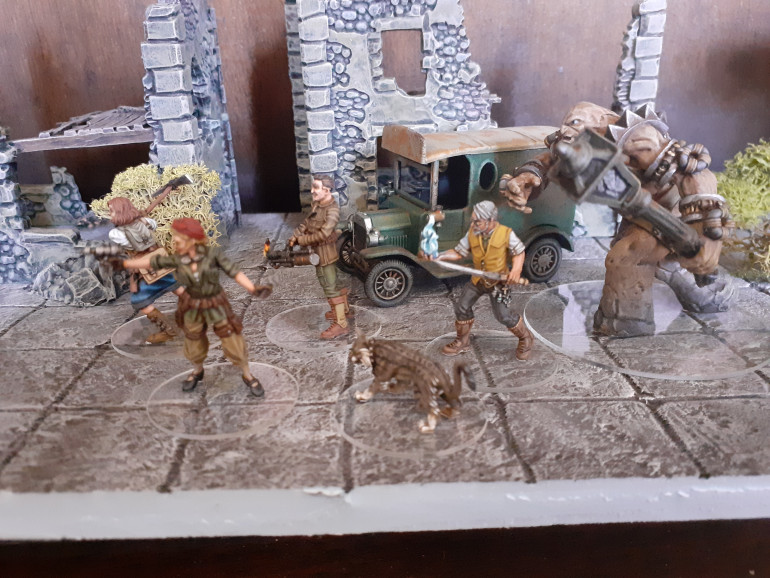 The miniatures displayed with some of the scenery I painted whilst waiting for my first order of Mythos models to arrive. The buildings are the Warlord plastic hamlet models and the van is a Lledo Walkers crisps promo model repainted.
