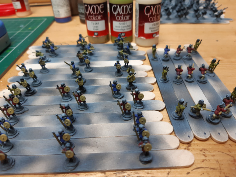 50/50 mix Khaki,camouflage green on the spears and shields. Followed by the 50/50 mix plus a few drops of bone white mixed in on the legs/feet