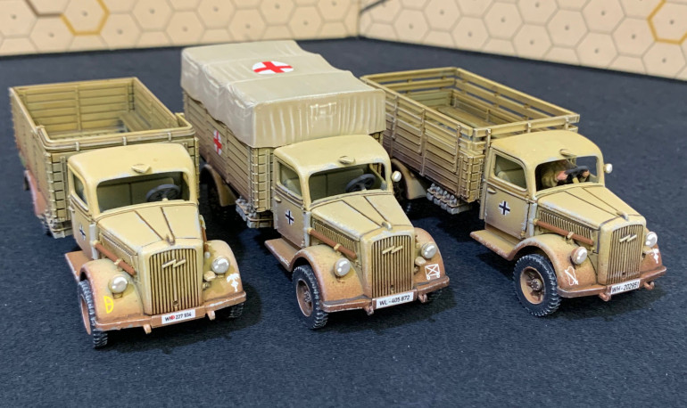 Markings are for (left to right) 21st Panzer Division, generic motorized infantry for the medic truck, and 90th Light Division for the truck on the right.