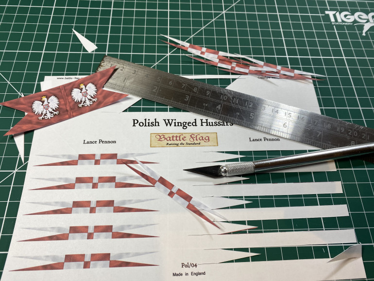To cut out paper flags I find a sharp blade and a metal ruler are the easiest things to use.
