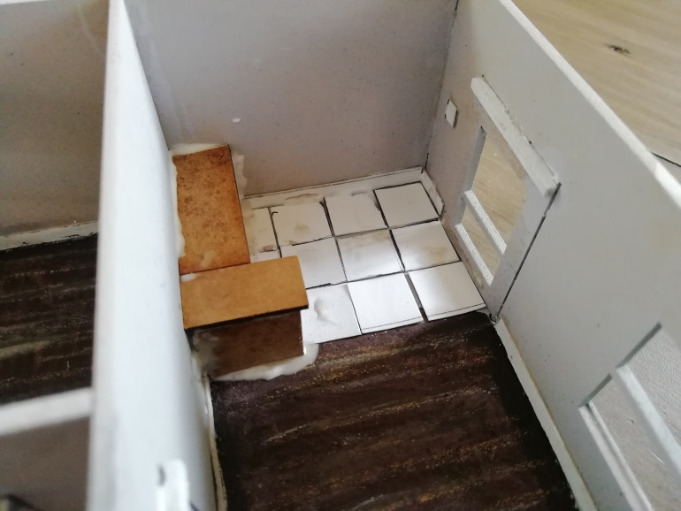 Work begins on the interior of one building. I've painted the floor and used crayons to draw in wood boards. I've built a little kitchen and tiled the floor with card