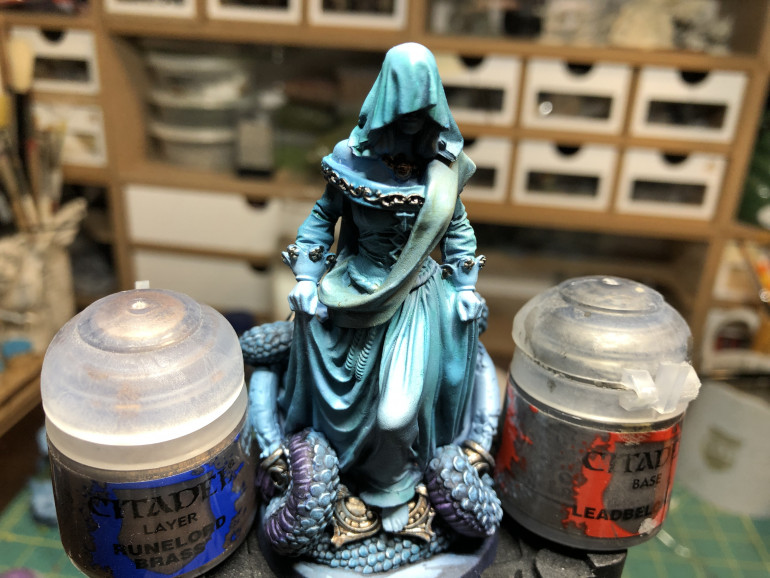 I decided to contrast the metallic part by using GW Leadbelcher on the dress decorations and GW Runelord Brass on the base shield links and the medallion. Be careful when applying the paint so as not to alter the environing garments and base components. Less is more as you are just going for a glint aspect rather than plain coverage.