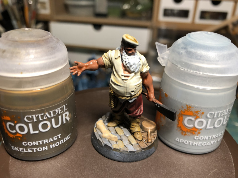 Gallery above (Left) - I used GW Zandri Dust for the belt, Vallejo Woodgrain for the cleaver handle and black for the cleaver blade. Gallery above (Right) - The back pouch was painted GW Gorthor Brown and the Rabbit GW Mechanicus Standard Grey. Above - Now that the colors are blocked, time to apply shades. I want the shirt to look dirty and applied a layer of GW Contrast Skeleton Horde. The for bear and hair, I used GW Contrast Apothecary White.