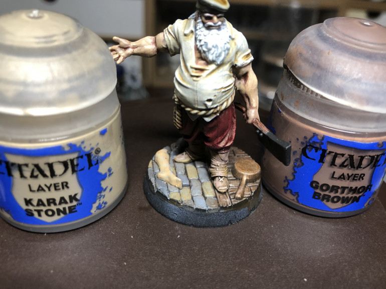 Gallery Abobr (LEft) - LEt the washes dry for about 1/2 hour to one hour and you are ready for highlights. Gallery Above (Right) - Pants are drybrished with a small drybrush and GW Khorne Red. Focus on the part of the pants that are hit by zenithal light. Dry Brush the part of the shirt exposed to zenithal light with white, along with the hair. Spot highlight the beard with white. Finally, spot brush the belt with GW Ushabti Bone. Above - Next dry brush the getters and shoes with GW Karak Stone and GW Gorthor Brown being careful not to touch the pants nor base.