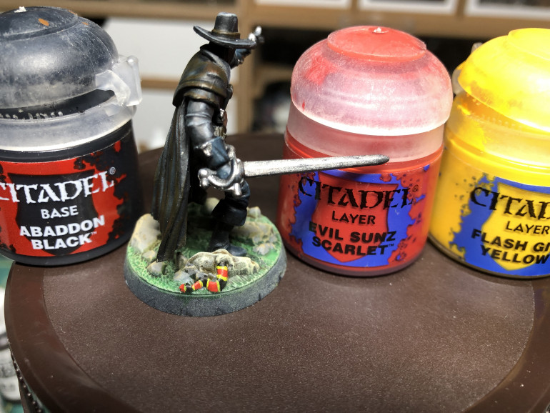 The base was painted with GW Contrast Ork Flesh (grass) , Abaddon Dune (stones) and SKeleton Horde (skulls). The grass is highlighted with GW Skarsnik Green, the stones with GFW Tallarn Sand and the  skulls with GW Ushabti Bone Finally, a coral snake was added using black, red and yellow for color and contrast with the dark miniature.