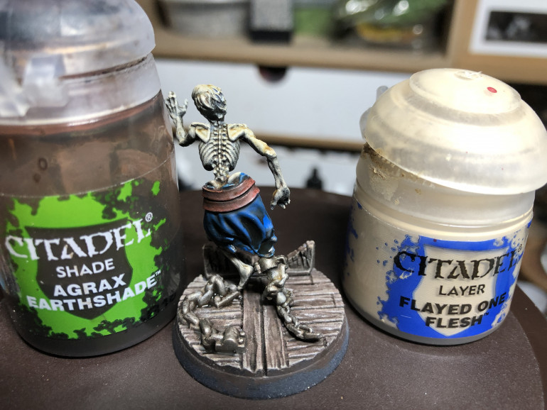 Apply a coat of GW Agrax Earthshade to the chains (to dull the shine and make them appear dusty and rusty-ish) as well as to the belt and rags. Drybrush the skeleton with GW Ushabti Bones on the surfaces exposed to zenithal light.