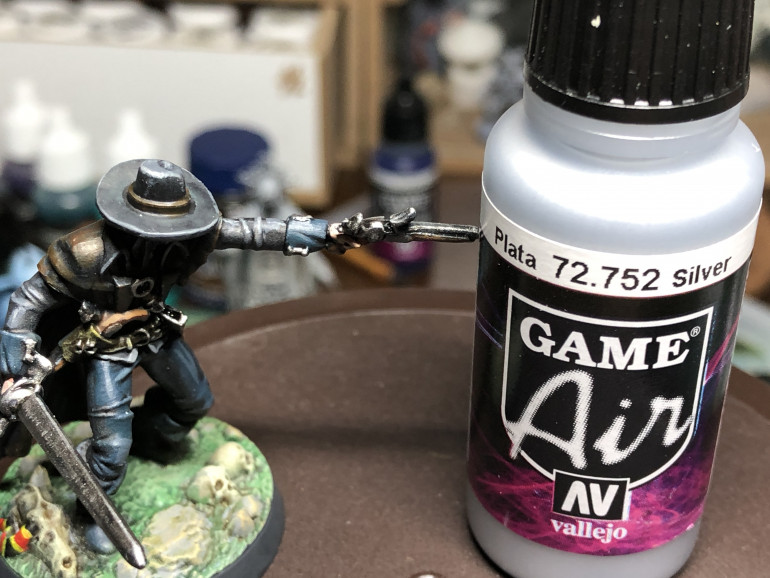 Metallic parts (pistols/buckles/sword) were given a layer of Leadbelcher and a wash of Nuln Oil Gloss. They are then  highlighted with Vallejo Air Silver. Ensure to only highlight teh pats hit by the zenithal light.