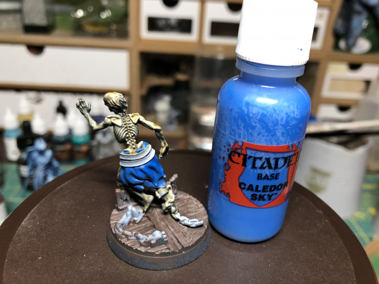 As the base and skeleton will have rather warm tones, I chose to color the ragged clothes blue, using GW Caledor Sky.