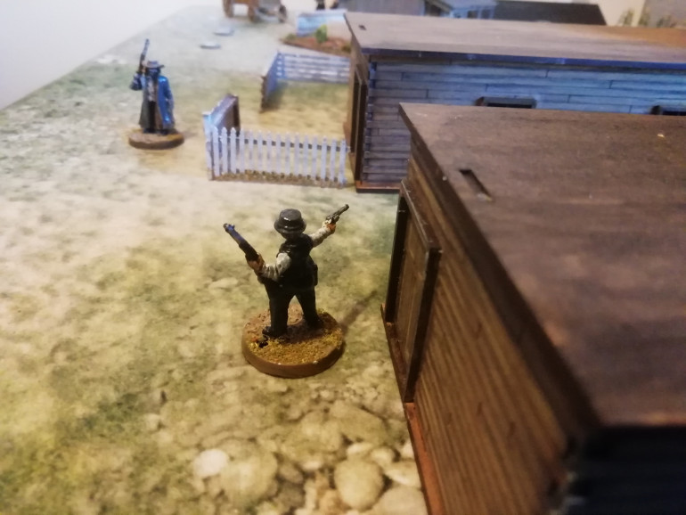 Leaving his deputy to keep the outlaws pinned down sheriff Ogelsby skirts the back streets and confronts a tough who unloads his sixshooter. All six shots fly by him but he Cooley stands his ground